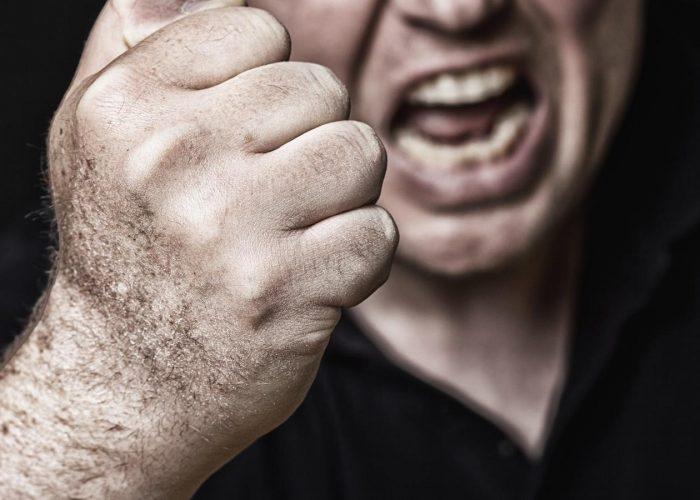 Ein Mann hebt aggressiv drohend die Faust.